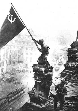 A Soviet officer waves their flag after a battle that has been won